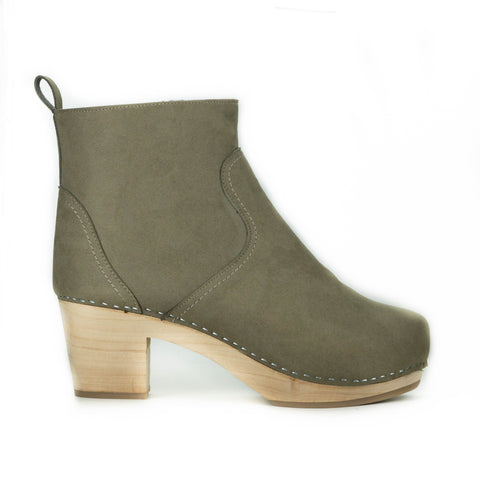 A taupe vegan suede clog bootie. Ankle height shaft with pull tab in back. Inside zipper closure. Blonde wooden sole. Staples around outsole to connect material to sole.