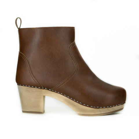 A tan vegan leather clog bootie. Ankle height shaft with pull tab in back. Inside zipper closure. Blonde wooden sole. Staples around outsole to connect material to sole.
