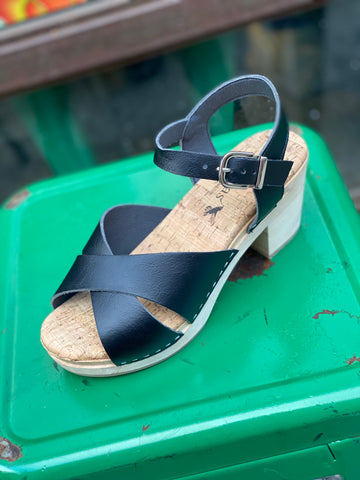 A heeled clog sandal, with black vegan leather straps that cross in front and an ankle strap with a silver buckle closure. Beige colored cork insole, blonde wooden sole and heel. On a green background.