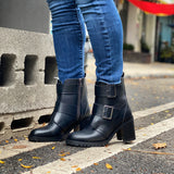 A pair of black vegan leather boots with a heel on a woman's legs wearing blue jeans. Street in background. . 2 large silver buckles on side, inside zipper closure.