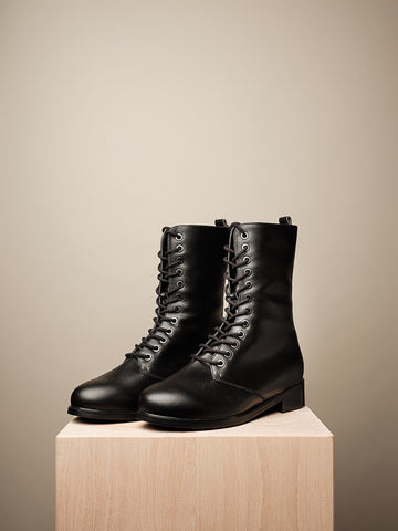 A pair of black lace up boots, mid-calf height. Pull tab in back, black sole. On a wooden pedestal.