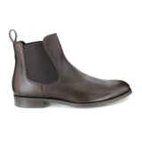 A dark brown vegan leather chelsea boot. Pull tab in back, elastic paneling on sides. Dark brown sole. Slightly tapered toe.