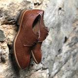 A tan vegan leather brogue dress shoe, lace up with 3 eyelets. Tan and dark brown sole with rubber grip for traction. Shown against a brick and concrete wall.