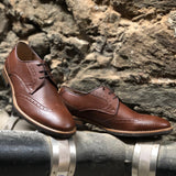 A tan vegan leather brogue dress shoe, lace up with 3 eyelets. Tan and dark brown sole with rubber grip for traction. Shown against a cement background.
