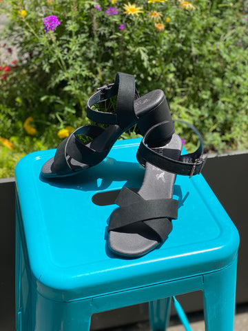 A pair of heeled sandals with black microsuede uppers and black lining and sole. Cross straps on top of foot, buckle closure at ankle. On a blue stool with foliage in background.