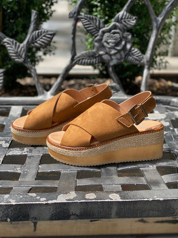 A pair of wedge sandals in tan, with cross straps and a buckle closure at the ankle. Jute and wooden tan sole.