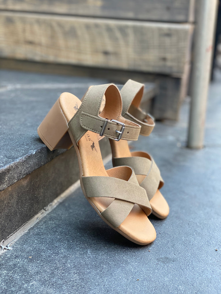 A pair of heeled sandals with beige microsuede uppers and tan lining and sole. Cross straps on top of foot, buckle closure at ankle.