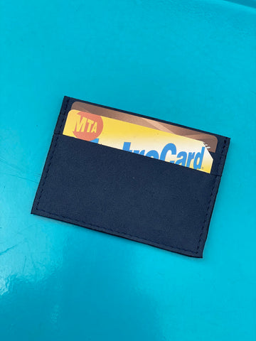Small cardholder in blue microsuede. 2 card slots on each side and slot in middle. Shown here with a card and Metrocard inside on a bright blue background.