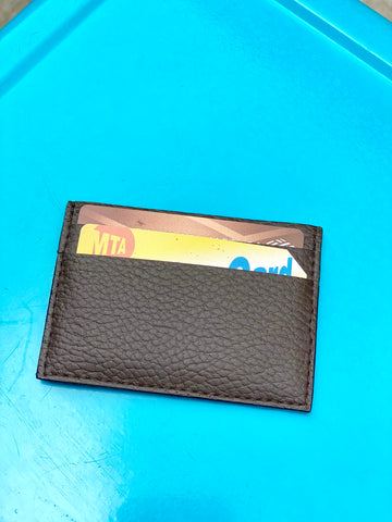 Small cardholder in brown pebbled vegan leather. 2 card slots on each side and slot in middle.  Shown here with a card and Metrocard inside on a blue background.