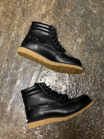 A pair of black vegan leather worker style, lace-up boots with a tan sole on a grey background.