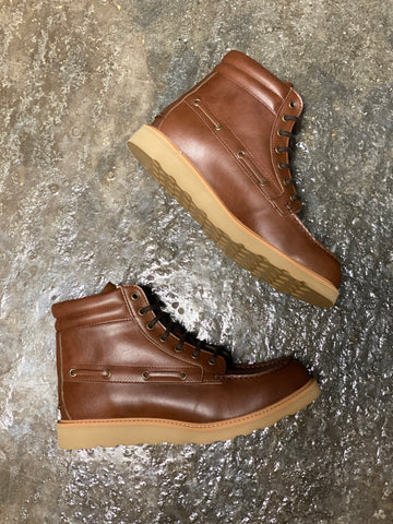 A pair of tan vegan leather worker style, lace-up boots with a tan sole on a grey background.