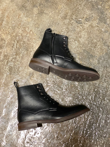 A pair of black vegan leather boots on their side on a grey background. Black laces and inside zipper closure, brown soles.