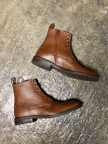 A pair of tan vegan leather boots on their side on a grey background. Black laces and inside zipper closure, brown soles.