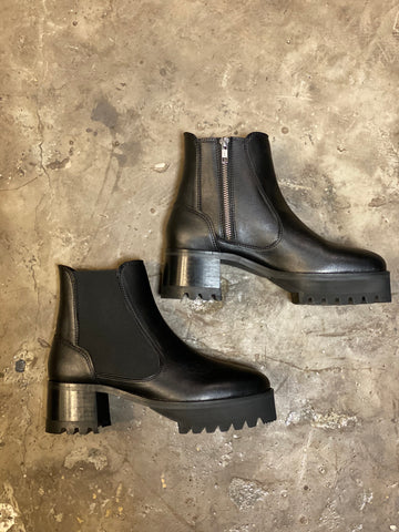 A pair of black vegan leather booties on a cement floor. Elastic paneling on side of boot and silver zipper on inside. Platform lug sole.