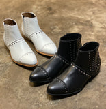 A pair of white and a pair of black vegan booties with silver stud detailing on a cement floor.