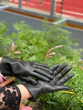 Black vegan leather gloves on a woman's hands with green foliage in the background