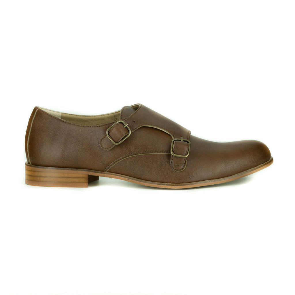 A tan vegan leather double monk shoe with two brass buckles on outer side of shoe. Tan sole, 0.5 inch heel. Rounded toe.