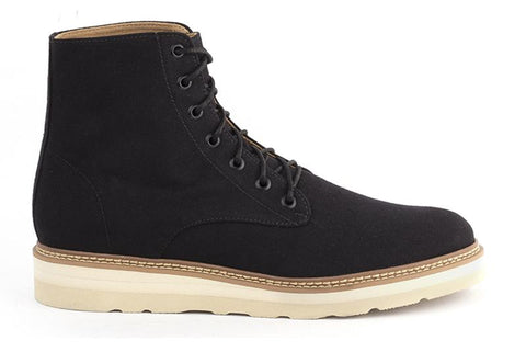 A lace up black canvas boot. 7 eyelets, black laces. Tan and beige vibram sole.