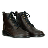 A pair of brown vegan leather boots with laces and brogue detailing. Black sole. On a white background.