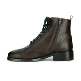A brown vegan leather boot with laces and brogue detailing. Inside zipper. Black sole. On a white background.