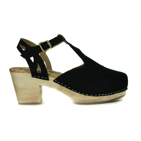 A t-strap style clog, black vegan suede uppers with a buckle closure at ankle. Cutout detailing on the back strap. Beige cork insole, blonde wooden sole. Staples to connect material to sole.
