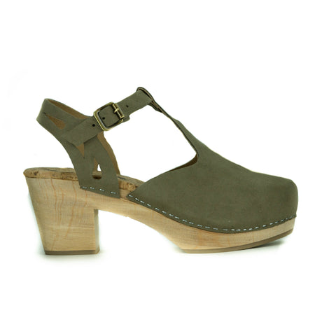 A t-strap style clog, taupe vegan suede uppers with a buckle closure at ankle. Cutout detailing on the back strap. Beige cork insole, blonde wooden sole. Staples to connect material to sole.