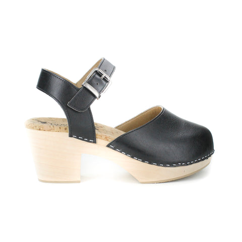 A mary jane style clog in black vegan leather. Ankle strap with silver buckle closure. Cork lining and blonde wood sole and heel. Silver staples attached upper to sole.