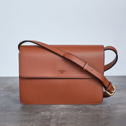 A rectangular crossbody bag with a top flap snap closure. In a burnt orange vegan leather. Adjustable crossbody strap with gold hardware.