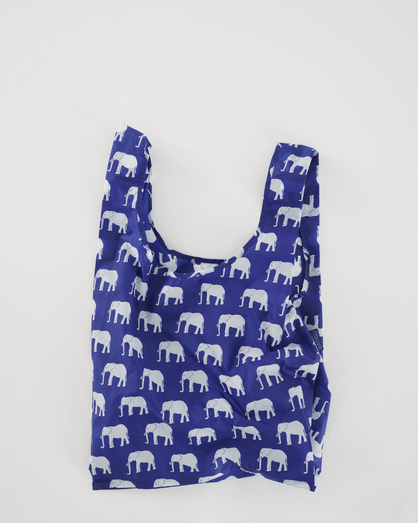 A reusable bag, blue with white elephants printed on it. Two shoulder handles.