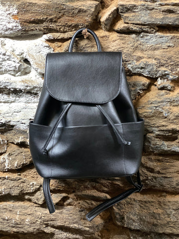 A black vegan leather backpack with a front flap and two side pockets hanging against a brick wall.
