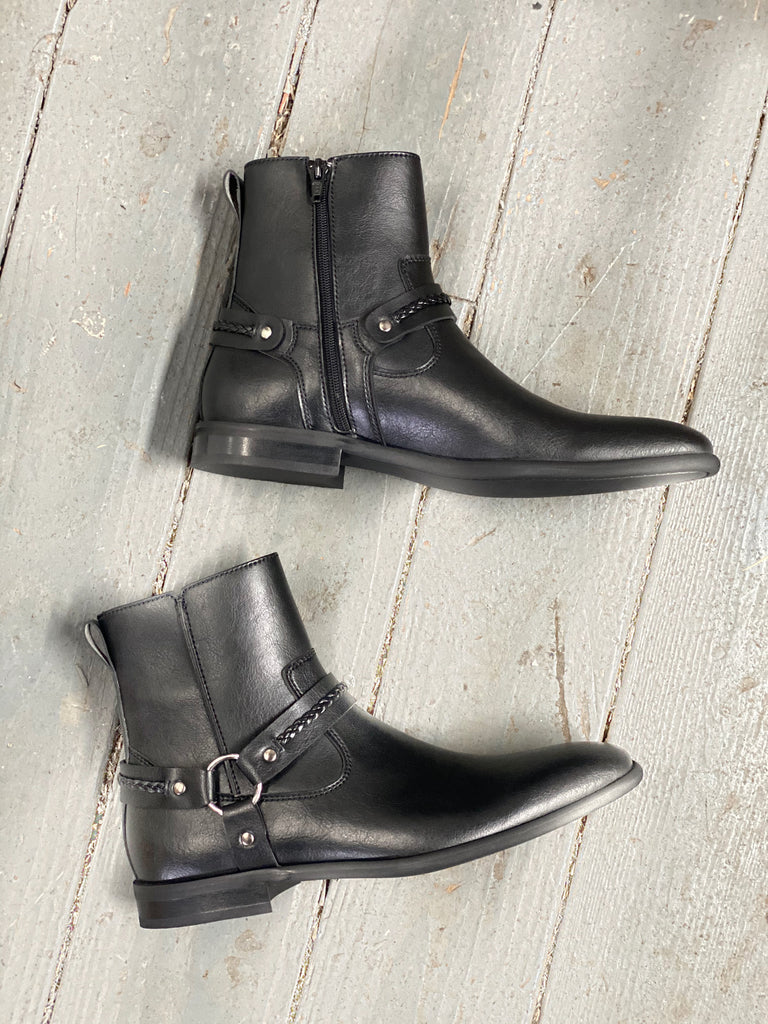 A pair of men's boots in black vegan leather, with an inside zipper and silver harness detailing at the ankle. Grey wooden background.