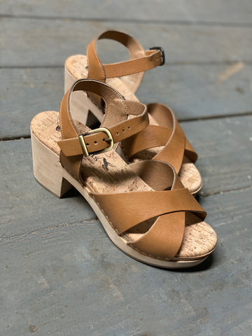 A pair of heeled clog sandals, with camel leather straps that cross in front and have an ankle strap with a brass buckle closure. Beige cork insole and blonde wooden sole.