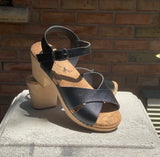 A heeled clog sandal, with black vegan leather straps that cross in front and an ankle strap with a silver buckle closure. Beige colored cork insole, blonde wooden sole and heel.