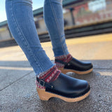 A pair of black vegan clogs with a backstrap on a woman's feet with chunky knit socks, subway platform in background.