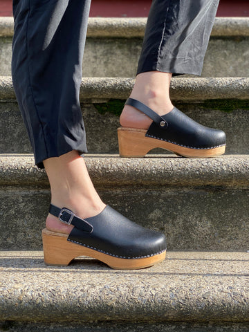 A pair of black vegan clogs with a backstrap, on a woman's feet on a flight of stairs.