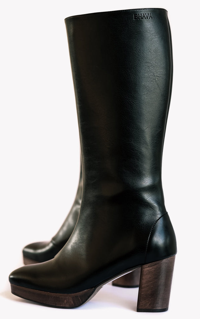 Knee high black vegan leather boots with a dark brown wooden heel and platform. Slightly pointed toe.