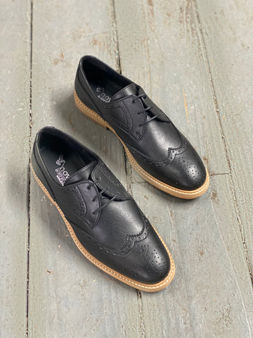A pair of black vegan leather brogues with a light tan sole on a grey background.