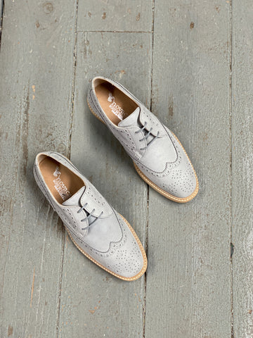 A pair of grey microsuede brogues with a light tan sole on a grey background.