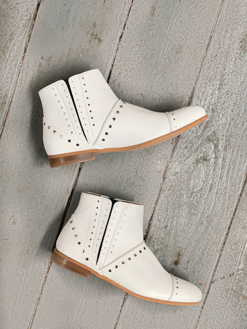 A pair of white vegan booties with silver stud detailing on a wooden floor.