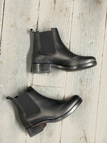 A pair of black vegan leather chelsea style booties on a grey background. Elastic paneling on sides of boots, black heel and sole.