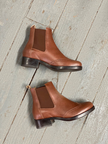 A pair of tan vegan leather chelsea style booties on a grey background. Elastic paneling on sides of boots, dark brown heel and sole.
