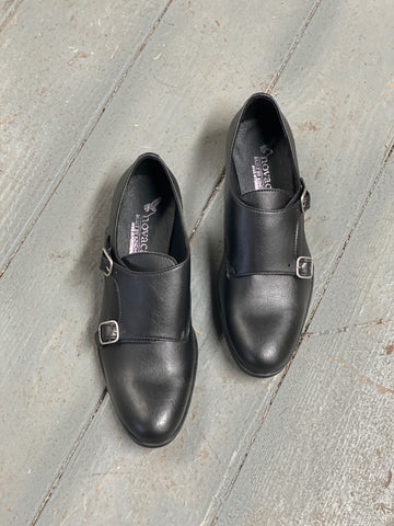 A pair of black vegan leather shoes with a double monk strap - 2 buckles - on a grey background.