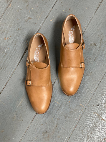 A pair of camel vegan leather shoes with a double monk strap - 2 buckles - on a grey background.