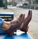 A tan vegan leather double monk shoe with two brass buckles on outer side of shoe. Tan sole, 0.5 inch heel. Rounded toe. Shown on a woman's feet with street in background.