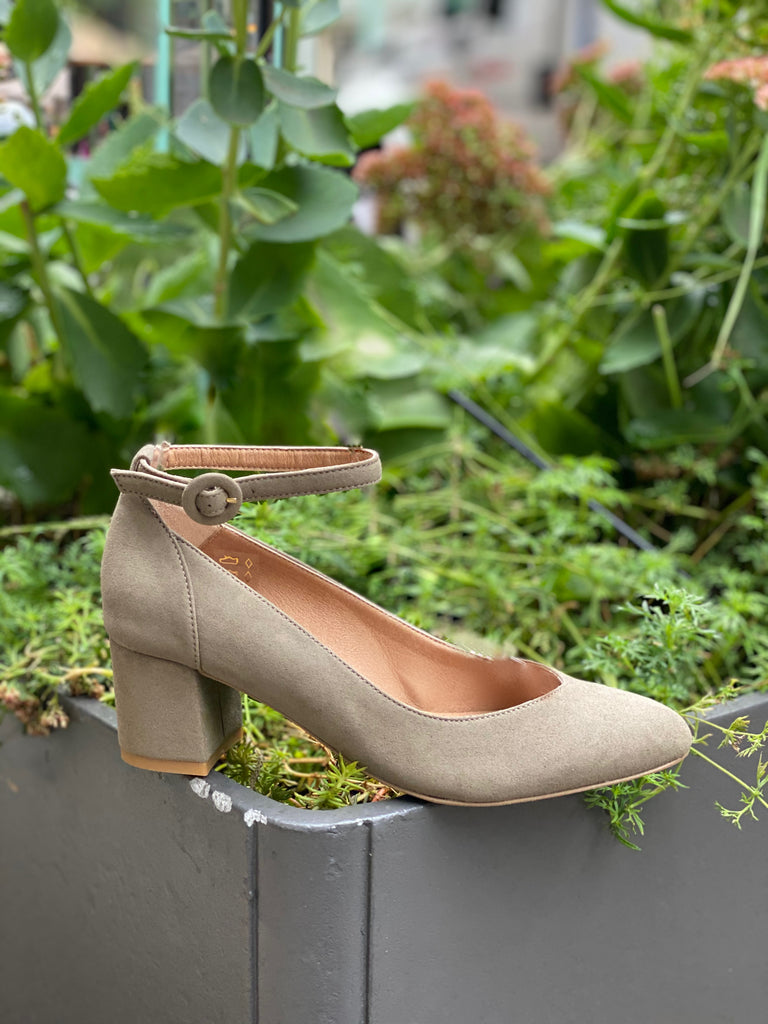 A taupe microsuede heel with an ankle strap and buckle closure, against a foliage background.