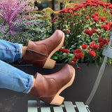 A pair of tan vegan leather clog booties on a woman's feet. Ankle height shaft with pull tab in back. Inside zipper closure. Blonde wooden sole. Staples around outsole to connect material to sole. Flowers in background.