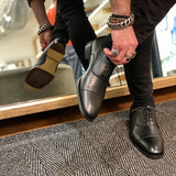 A black vegan leather men's dress shoe with a cap toe. Slightly tapered toe. Lace up with 5 eyelets. Black lining and sole. Shown on a man's feet with a mirror in the background to show the bottom of the sole.