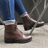 A pair of brown vegan leather boots with laces and brogue detailing on a woman's feet.