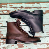 One black and one brown vegan leather lace up boot with brogue detailing, lying flat on a seafoam green background.
