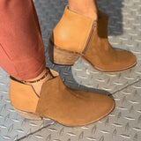 A pair of tan microsuede booties with a stacked wooden heel on a woman's feet. Grey background.